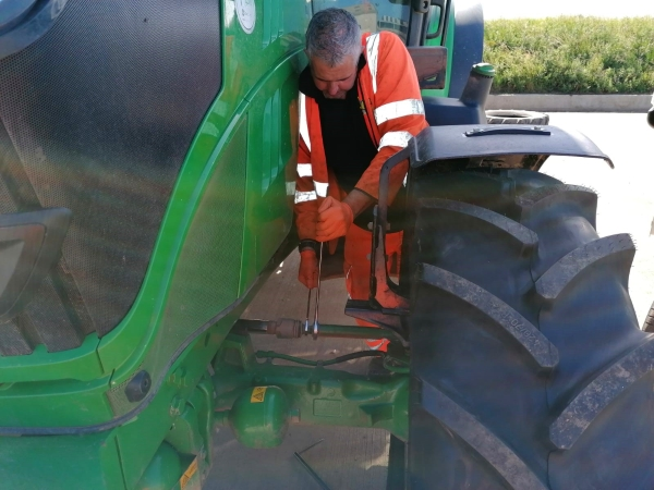 Technician adjusting the front toe setting on a John Deere tractor | Tractor Wheel Alignment | Bush Tyres