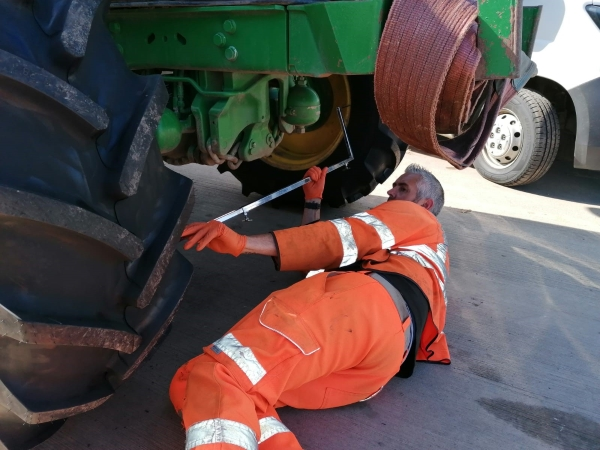 Technician measuring the front toe setting on a John Deere tractor | Tractor Wheel Alignment | Bush Tyres