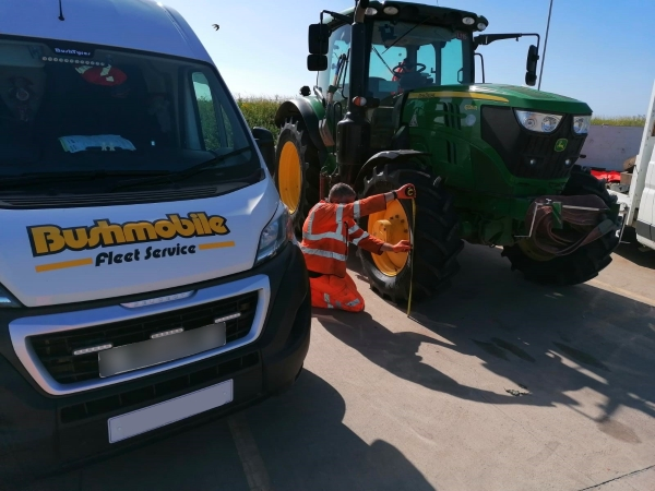 Technician measuring the front wheel alignment on a John Deere tractor | Tractor Wheel Alignment | Bush Tyres